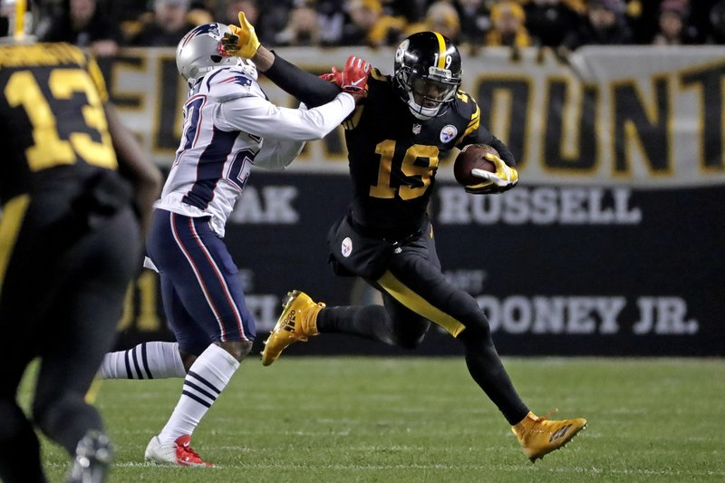 Pittsburgh Steelers wide receiver JuJu Smith-Schuster (19) stiff-arms New England Patriots defensive back J. (27) after catching a pass from quarterback Ben Roethlisberger during the first half of an NFL football game in Pittsburgh, Sunday, Dec. 16, 2018. (AP Photo/Don Wright)