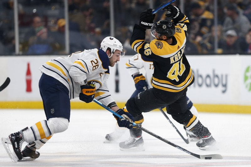 Buffalo Sabres' Zemgus Girgensons (28) gains control of the puck from Boston Bruins' David Krejci (46) during the first period of an NHL hockey game in Boston, Sunday, Dec. (AP Photo/Michael Dwyer)