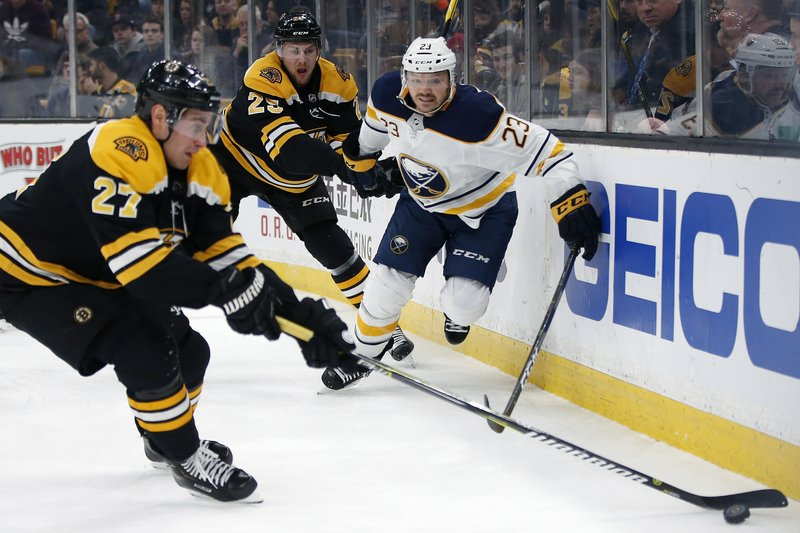 Buffalo Sabres' Sam Reinhart (23) battles for the puck with Boston Bruins' John Moore (27) and Brandon Carlo (25) during the first period of an NHL hockey game in Boston, Sunday, Dec. (AP Photo/Michael Dwyer)