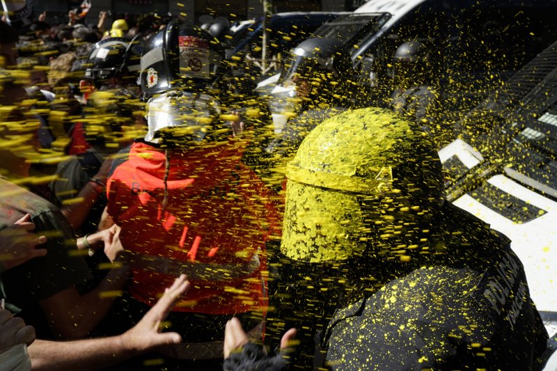 FILE - In this Saturday, Sept. 29, 2018 file photo pro-independence demonstrators throw paint at Catalan police officers during clashes in Barcelona, Spain. (AP Photo/Daniel Cole, File)