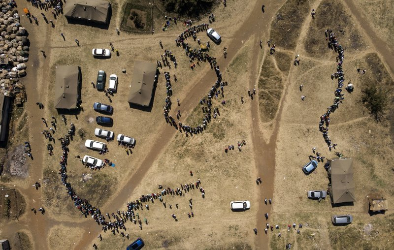 FILE - In this Monday, July 30, 2018 file photo people wait in a queue to cast their vote at a polling station in Harare, Zimbabwe. (AP Photo/Bram Janssen, File)