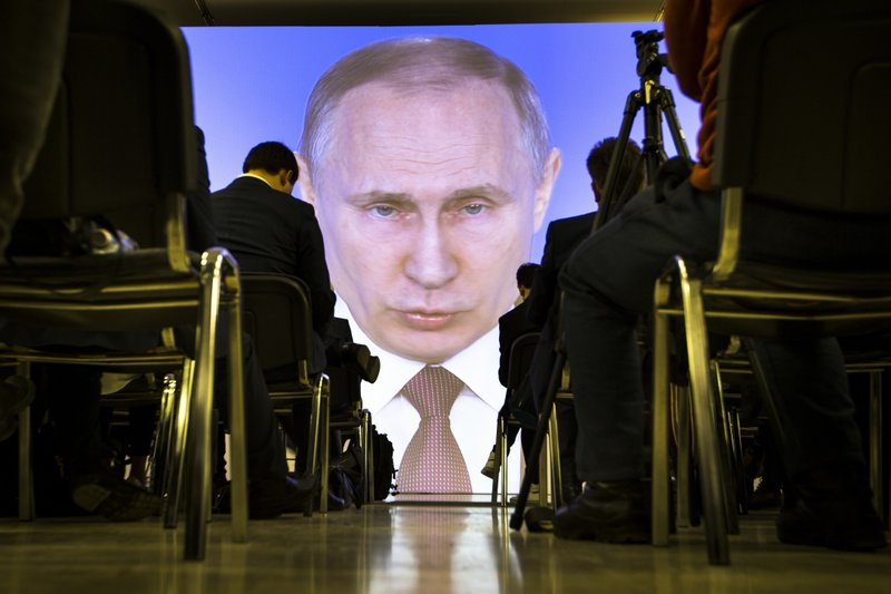 FILE - In this Thursday, March 1, 2018 file photo journalists watch as Russian President Vladimir Putin gives his annual state of the nation address in Manezh in Moscow, Russia. (AP Photo/Alexander Zemlianichenko, File)