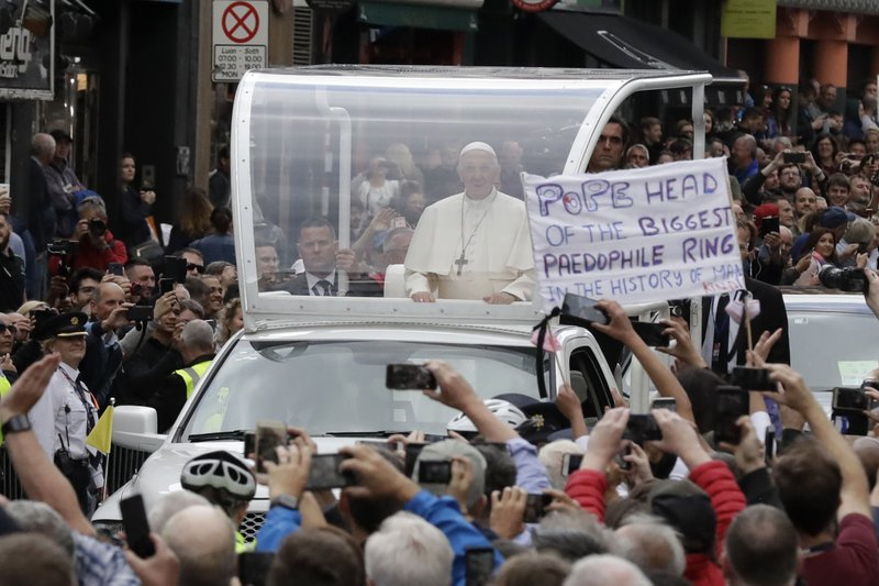 FILE - In this Saturday, Aug. 25, 2018 file photo Pope Francis passes by a banner of a protester as he leaves after visiting St Mary's Pro-Cathedral, in Dublin, Ireland. (AP Photo/Matt Dunham, File)