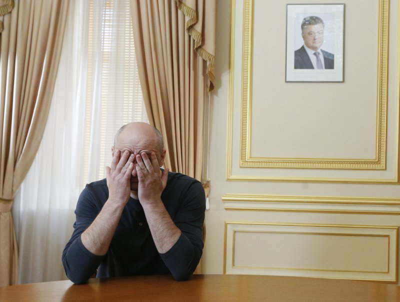 FILE - In this Thursday, May 31, 2018 file photo Russian journalist Arkady Babchenko holds his face during an interview with foreign media, with the portrait of Ukrainian President Petro Poroshenko, right in the background, in Kiev, Ukraine. (Valentyn Ogirenko/Pool Photo via AP, File)