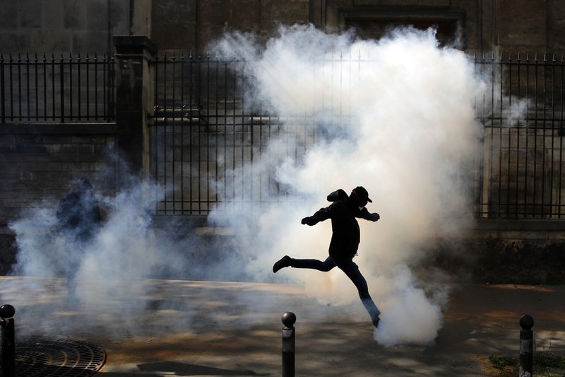 FILE - In this April 19, 2018 file photo an activist kicks a tear canister gas shot by riot police during a protest in support of the French railway employees, in Paris, France. (AP Photo/Francois Mori, File)