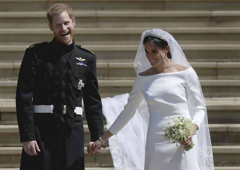 FILE - In this Saturday, May 19, 2018 file photo Meghan Markle and Britain's Prince Harry stand on the steps of St George's Chapel at Windsor Castle following their wedding in Windsor, near London, England. (Jane Barlow/pool photo via AP, File)