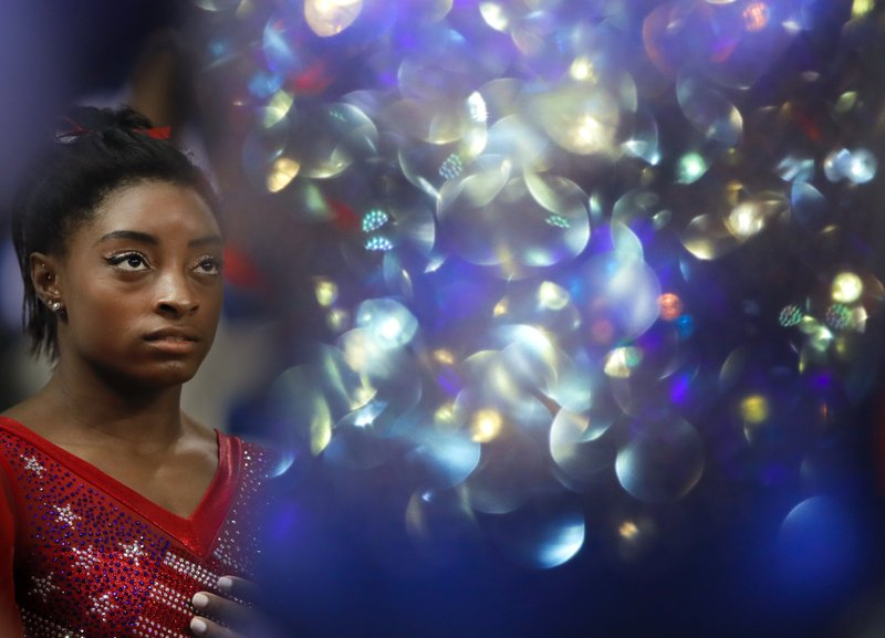 FILE - In this Tuesday, Oct. 30, 2018 file photo new world champion Simone Biles of the U.S. waits for the medal ceremony as the light bounces off a Russian gymnasts suit after the women's team final of the Gymnastics World Chamionships at the Aspire Dome in Doha, Qatar. (AP Photo/Vadim Ghirda, File)