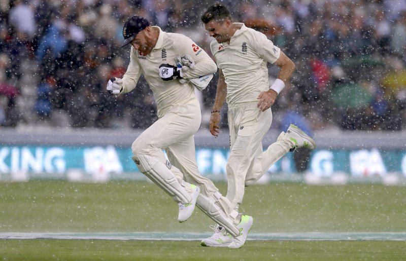 FILE - In this Friday, Aug. 10, 2018 file photo England's Jonny Bairstow and England's James Anderson run off the pitch as sudden heavy rain starts during the second day of the second test match between England and India at Lord's cricket ground in London. (AP Photo/Kirsty Wigglesworth, File)