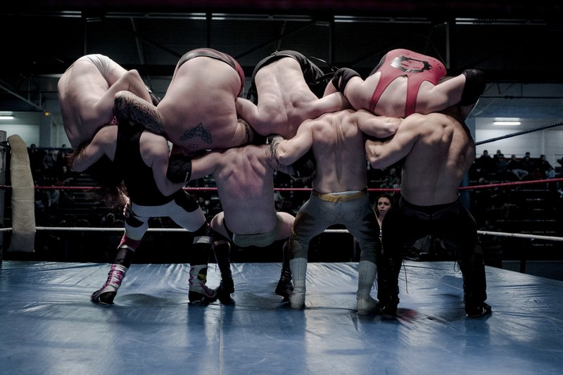 In this photo dated Saturday, Feb. 24, 2018 (L to R) wrestlers Nelson Fernandes, Alex Legrand, Ace Angel, and Zach, bottom, headlock wrestlers Lord Steven Crowley, Darkmundo, Maeven, and PV Red, fight during a wrestling charity gala in Ivry-sur-Seine, south of Paris, France. (AP Photo/Kamil Zihnioglu)