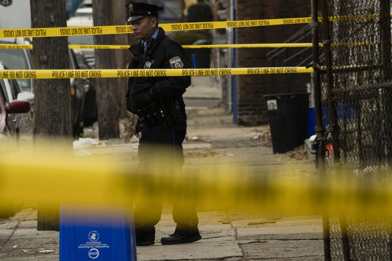 FILE - In this Dec. 14, 2018, file photo, a police officer stands guard outside a home where a woman was murdered on Woodstock Street in Philadelphia. (AP Photo/Matt Rourke, File)