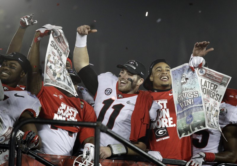 FILE - In this Jan. 1, 2018 file photo Georgia players hold up newspapers as they celebrate after they defeated Oklahoma 54-48 in overtime in the Rose Bowl NCAA college football game in Pasadena, Calif. (AP Photo/Jae C. Hong, file)