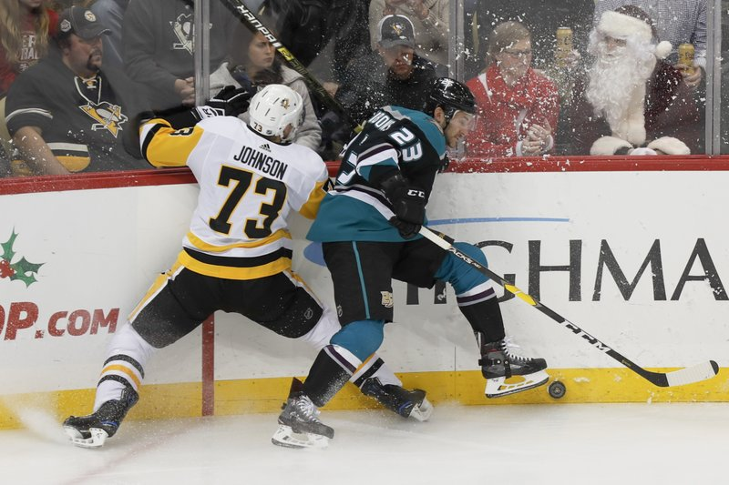Pittsburgh Penguins' Jack Johnson (73) and Anaheim Ducks' Brian Gibbons (23) battle for the puck along the boards during the first period of an NHL hockey game, Monday, Dec. (AP Photo/Keith Srakocic)