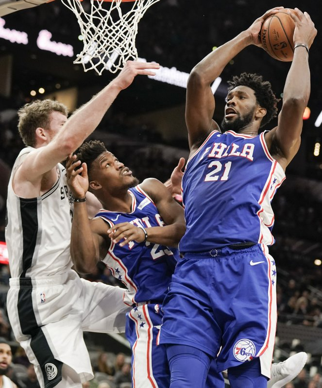 Philadelphia 76ers' Joel Embiid (21) shoots as 76ers' Jimmy Butler, center, and San Antonio Spurs' Jakob Poeltl look on during the first half of an NBA basketball game, Monday, Dec. (AP Photo/Darren Abate)