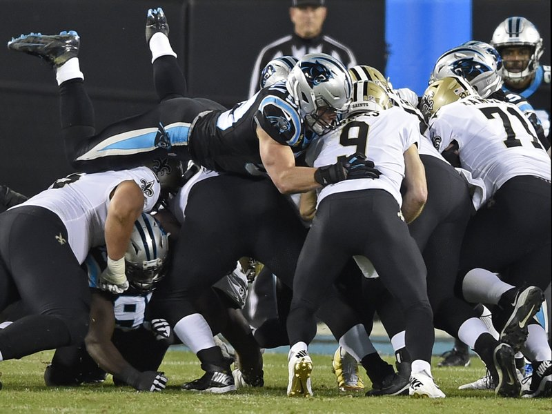 Carolina Panthers' Luke Kuechly, top left, leaps over the line to sack New Orleans Saints' Drew Brees (9) in the first half of an NFL football game in Charlotte, N. (AP Photo/Mike McCarn)