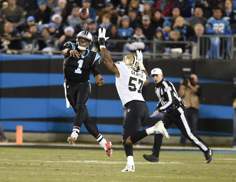 Carolina Panthers' Cam Newton (1) throws a pass as New Orleans Saints' Alex Okafor (57) defends in the first half of an NFL football game in Charlotte, N. (AP Photo/Mike McCarn)