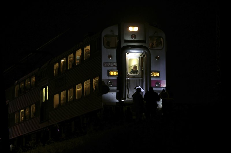 Passengers sit on a train while police officers work the scene where two officers were killed after they were struck by a South Shore train near 103rd Street and Dauphin Avenue on Monday, Dec. (E. Jason Wambsgans/Chicago Tribune via AP)