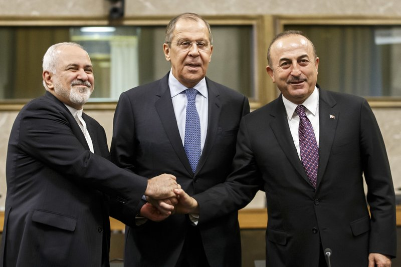 Iranian Foreign Minister Mohammad Javad Zarif, left, Russian Foreign Minister Sergei Lavrov, center, and Turkish Foreign Minister Mevlut Cavusoglu, right, shakes hands after a joint statement following the consultations on Syria, at the European headquarters of the United Nations in Geneva, Switzerland, Tuesday, Dec. (Salvatore Di Nolfi/Keystone via AP)