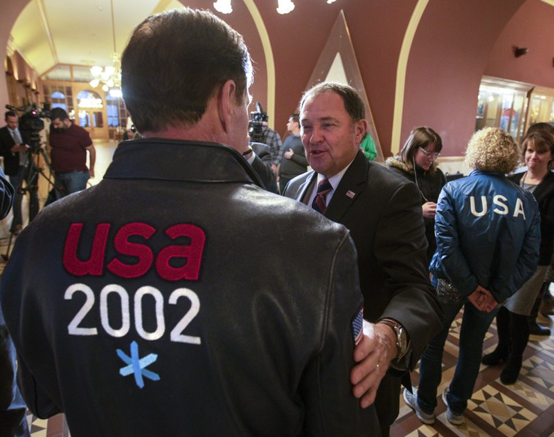 Gov. Gary Herbert, center, talks with Fraser Bullock, chief operating officer of the 2002 Winter Games, after the USOC choose Salt Lake over Denver to bid on behalf of the US for future Winter Games, Friday, Dec. (Steve Griffin/The Deseret News via AP)