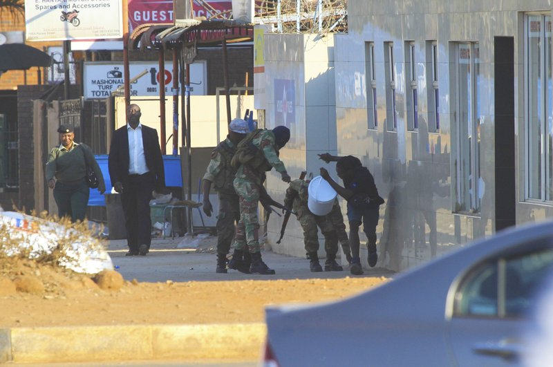 FILE - In this Aug, 1, 2018 file photo, soldiers use whips to assault people in Harare, Zimbabwe, following demonstrations by opposition party supporters. (AP Photo/Tsvangirayi Mukwazhi)