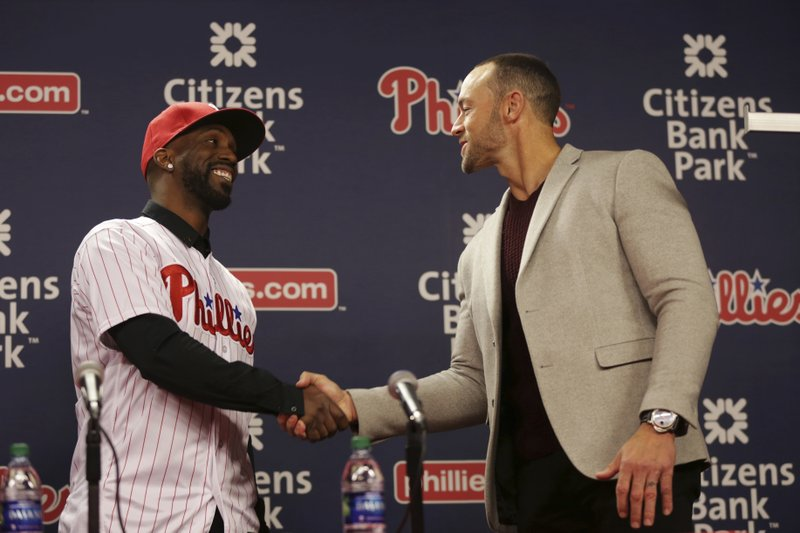 Philadelphia Phillies new outfielder Andrew McCutchen, left, shakes hands with manager Gabe Kapler during a news conference in Philadelphia, Tuesday, Dec. (AP Photo/Matt Rourke)