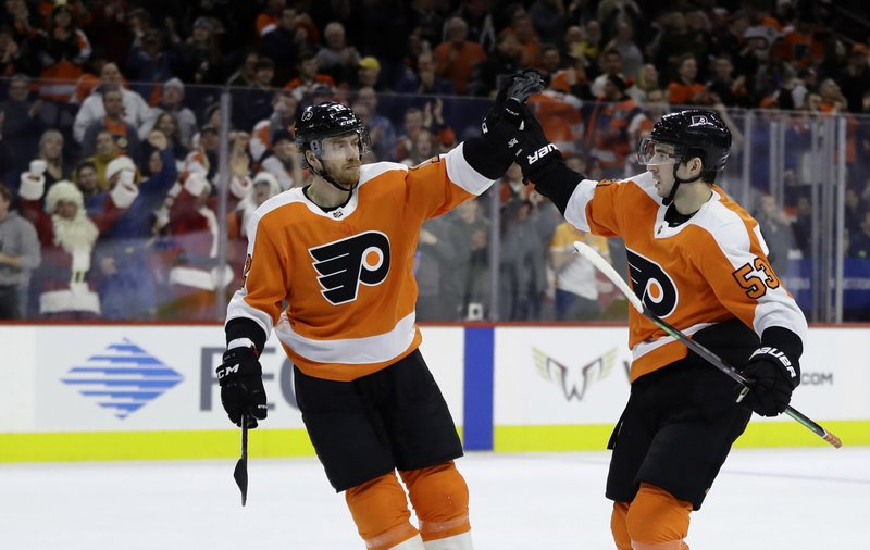 Philadelphia Flyers' Shayne Gostisbehere, right, and Michael Raffl celebrate after a goal by Gostisbehere during the second period of an NHL hockey game against the Detroit Red Wings, Tuesday, Dec. (AP Photo/Matt Slocum)
