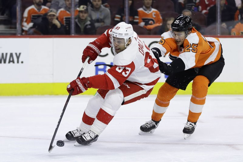Philadelphia Flyers' James van Riemsdyk, right, hooks Detroit Red Wings' Trevor Daley during the first period of an NHL hockey game, Tuesday, Dec. (AP Photo/Matt Slocum)