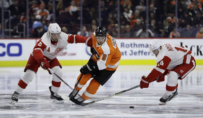 Philadelphia Flyers' Ivan Provorov (9) and Detroit Red Wings' Justin Abdelkader (8) and Gustav Nyquist (14) chase after a loose puck during the second period of an NHL hockey game, Tuesday, Dec. (AP Photo/Matt Slocum)
