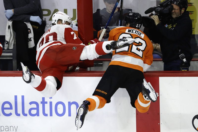 Detroit Red Wings' Christoffer Ehn, left, and Philadelphia Flyers' Dale Weise fly into the bench after a collision during the third period of an NHL hockey game, Tuesday, Dec. (AP Photo/Matt Slocum)