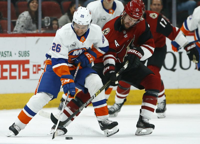 New York Islanders right wing Joshua Ho-Sang (26) tries to keep the puck away from Arizona Coyotes center Derek Stepan, right, during the first period of an NHL hockey game Tuesday, Dec. (AP Photo/Ross D. Franklin)
