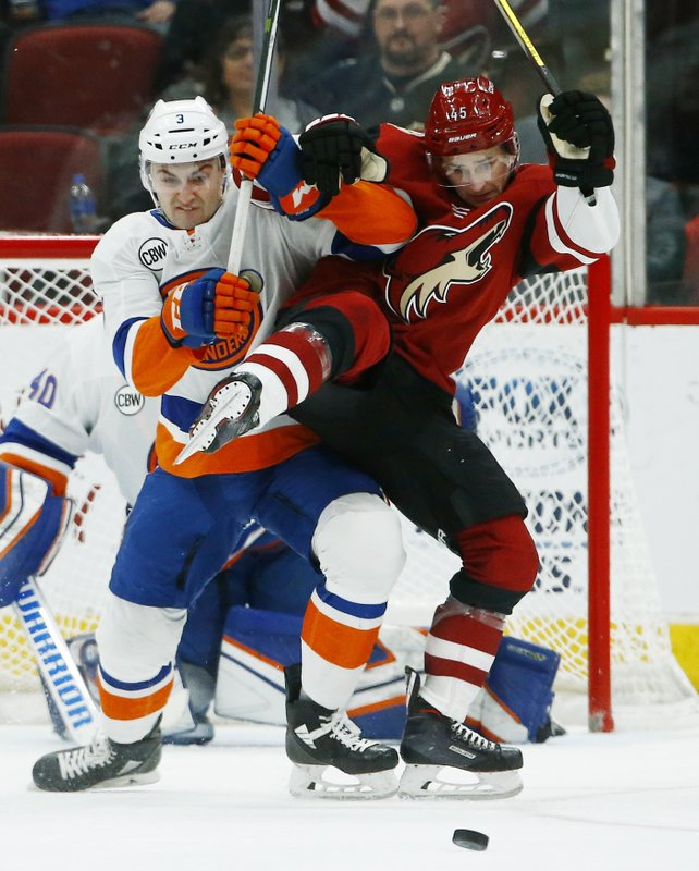 New York Islanders defenseman Adam Pelech (3) battles with Arizona Coyotes right wing Josh Archibald (45) during the first period of an NHL hockey game Tuesday, Dec. (AP Photo/Ross D. Franklin)