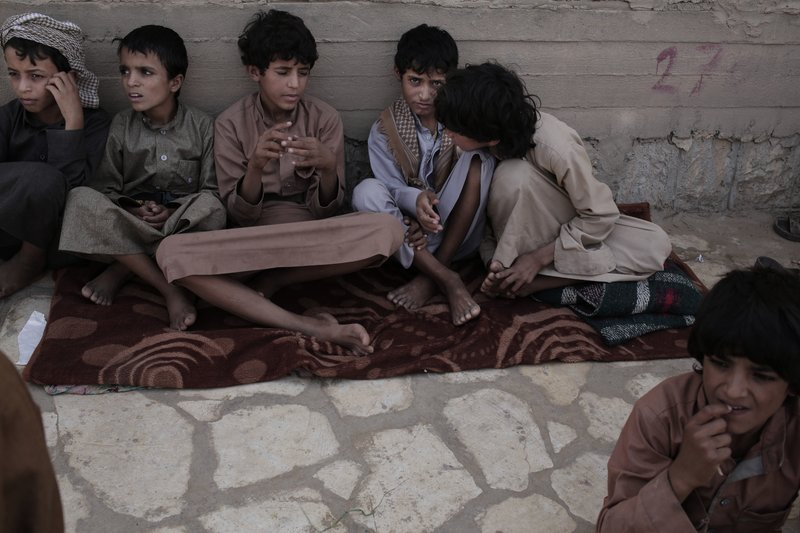 In this July 27, 2018, photo, 14 year-old Abdel Hamid, second right, and 14 year-old Morsal, third right, sit at a camp for displaced persons where they took shelter, in Marib, Yemen. (AP Photo/Nariman El-Mofty)