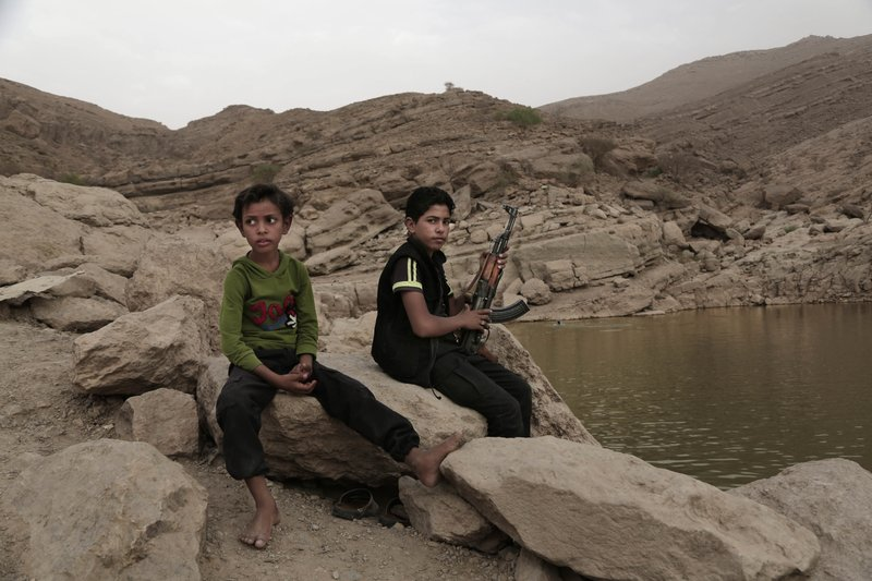"""In this July 30, 2018, photo, a 17 year-old boy holds his weapon in High dam in Marib, Yemen. Experts say child soldiers are """"the firewood"""" in the inferno of Yemen's civil war, trained to fight, kill and die on the front lines. (AP Photo/Nariman El-Mofty)"""