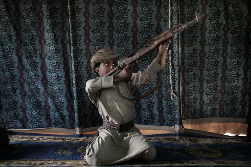 Kahlan, a 12-year-old former child soldier, demonstrates how to use a weapon, at a camp for displaced persons where he took shelter with his family, in Marib, Yemen in this July 27, 2018 photo. (AP Photo/Nariman El-Mofty)