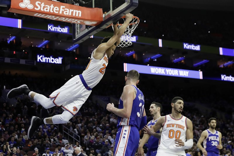 New York Knicks' Kevin Knox, left, hangs on the rim after a dunk against Philadelphia 76ers' Mike Muscala during the first half of an NBA basketball game, Wednesday, Dec. (AP Photo/Matt Slocum)