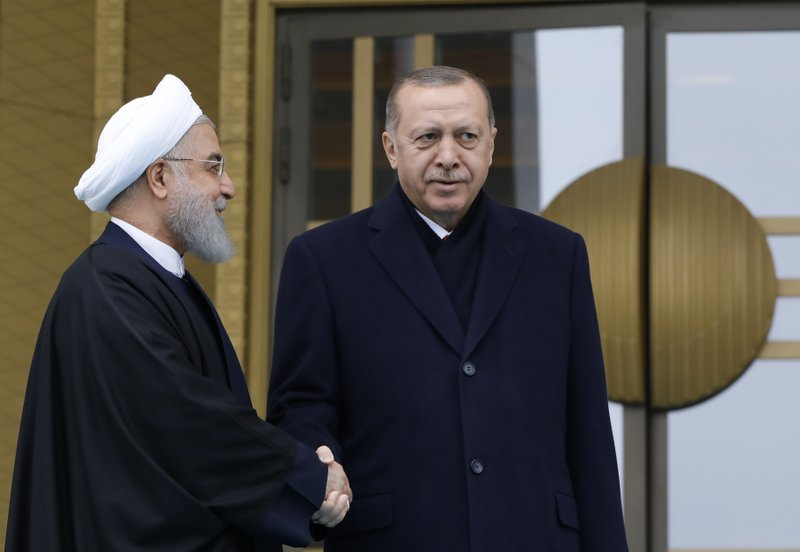 Turkey's President Recep Tayyip Erdogan, right and Iran's President Hassan Rouhani, left, shake hands prior to their talks at the Presidential Palace in Ankara, Thursday, Dec. (AP Photo/Burhan Ozbilici)