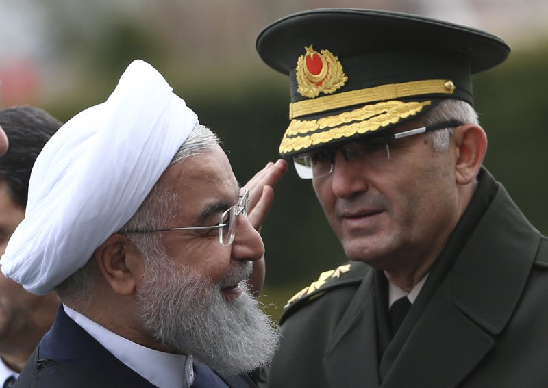Iran's President Hassan Rouhani reviews an honour guard during the welcome ceremony by Turkey's President Recep Tayyip Erdogan, prior to their talks at the Presidential Palace in Ankara, Thursday, Dec. (AP Photo/Burhan Ozbilici)