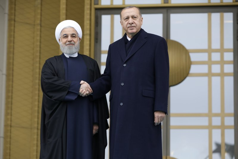 Turkey's President Recep Tayyip Erdogan, right and Iran's President Hassan Rouhani, left, shakes hands prior to their talks at the Presidential Palace in Ankara, Thursday, Dec. (AP Photo/Burhan Ozbilici)