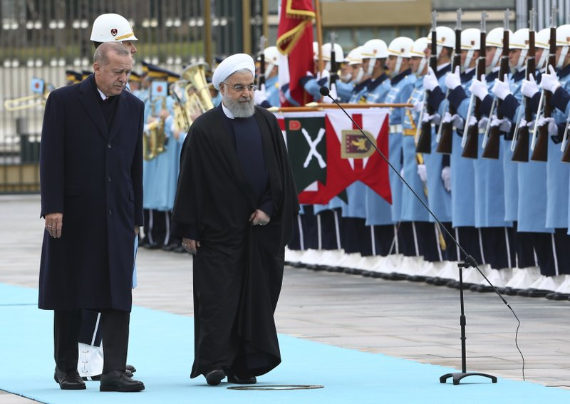 Turkey's President Recep Tayyip Erdogan, left and Iran's President Hassan Rouhani, centre, review an honour guard during the welcome ceremony, prior to their talks at the Presidential Palace in Ankara, Thursday, Dec. (AP Photo/Burhan Ozbilici)