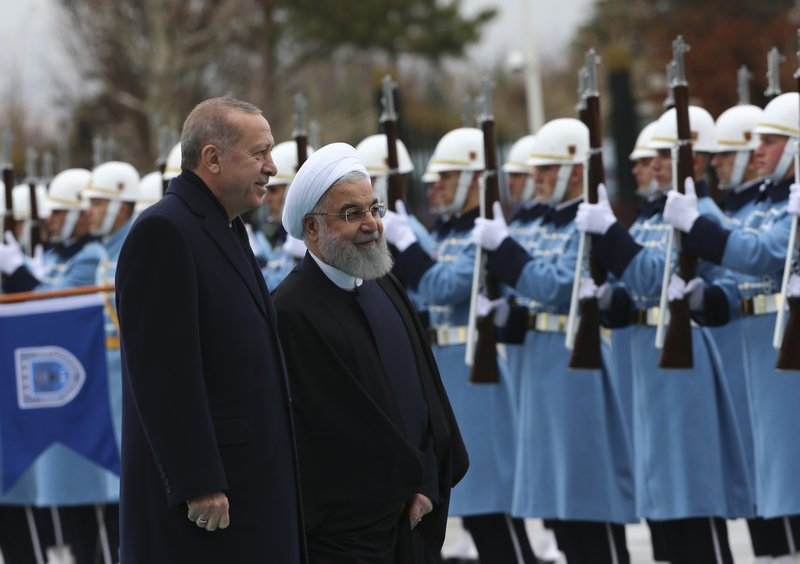 Turkey's President Recep Tayyip Erdogan, left, and Iran's President Hassan Rouhani, centre, review an honour guard during the welcome ceremony, prior to their meeting at the Presidential Palace in Ankara, Thursday, Dec. (AP Photo/Burhan Ozbilici)