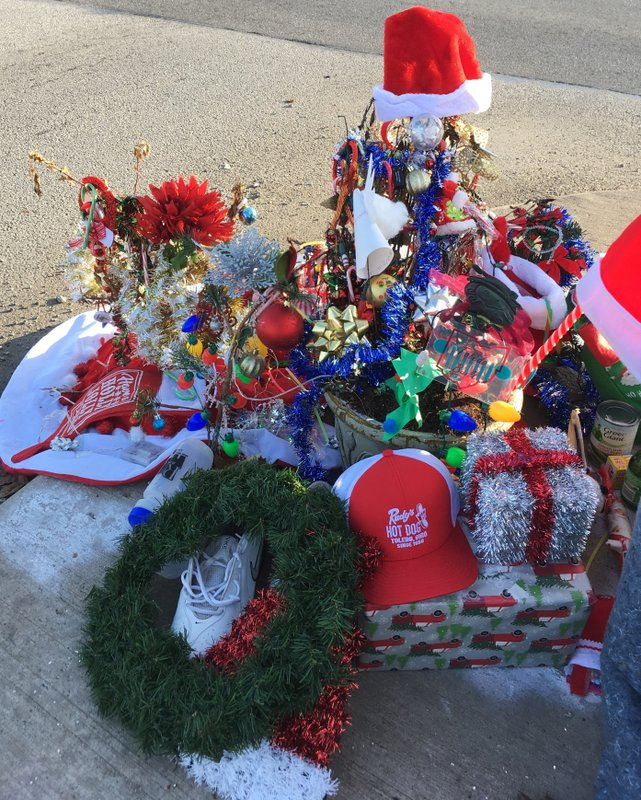 In this Dec. 18, 2018 photo, Christmas decorations and donations surround what's now known as the Christmas weed in Toledo, Ohio. (AP Photo/John Seewer)