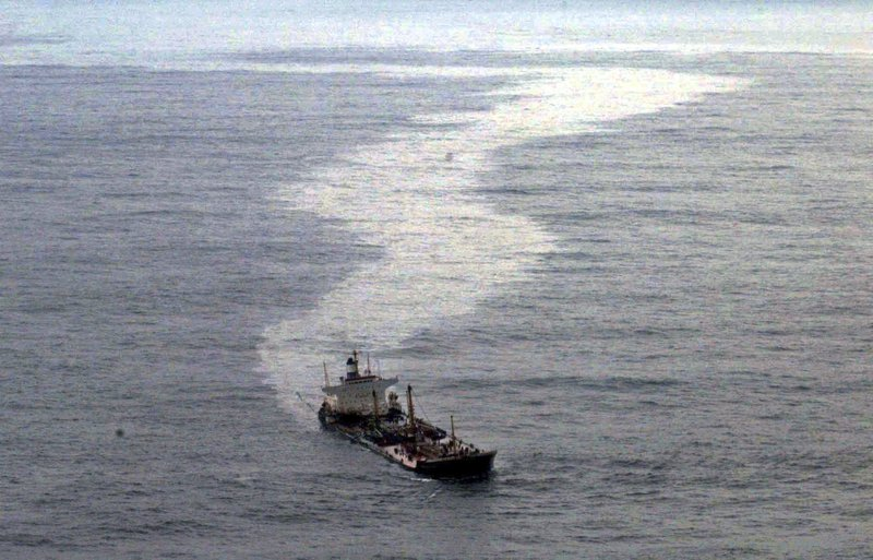 FILE - In this Nov. 14, 2002 file photo, the stricken Bahamas-flagged Prestige, carrying some 77,000 metric tons (85,000 US tons) of fuel oil, leaves a trail of oil behind it off the northwestern Spanish coast near the town of Muxia, Spain. (AP Photo/Carmelo Alen, File)