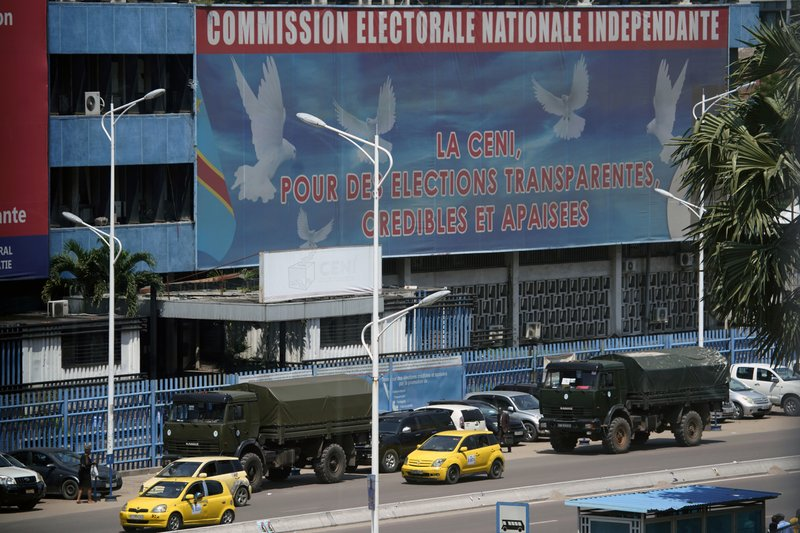 In this photo taken Tuesday Dec. 18, 2018, Military truck used to carry voting equipment are park outside the independent electoral commission (CENI) in Kinshasa, Democratic Republic of the Congo. (AP Photo/Jerome Delay)