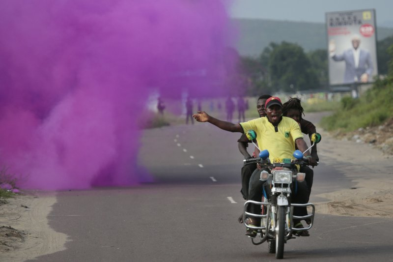 Supporters of opposition candidate Martin Fayulu run from tear gas fired by police in Nsele, 50kms east of Kinshasa, Democratic Republic of the Congo, Wednesday Dec. (AP Photo/Jerome Delay)