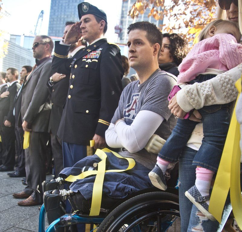 """former U.S. Air Force Senior Airman Brian Kolfage, center, sits in a wheelchair next to his wife Ashley, right, who holds their daughter Paris, during the National September 11 Memorial and Museum's """"Salute to Service"""" tribute honoring U. (AP Photo/Bebeto Matthews, file)"""
