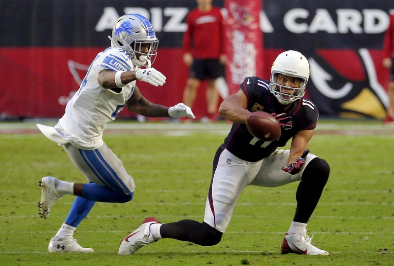 FILE - In this Sunday, Dec. 9, 2018, file photo, Arizona Cardinals wide receiver Larry Fitzgerald (11) makes his 1,282nd career catch to surpass NFL Hall of Famer Jerry Rice for the most receptions with one team in NFL history during the second half of an NFL football game as Detroit Lions cornerback Nevin Lawson (24) defends in Glendale, Ariz. (AP Photo/Rick Scuteri, File)