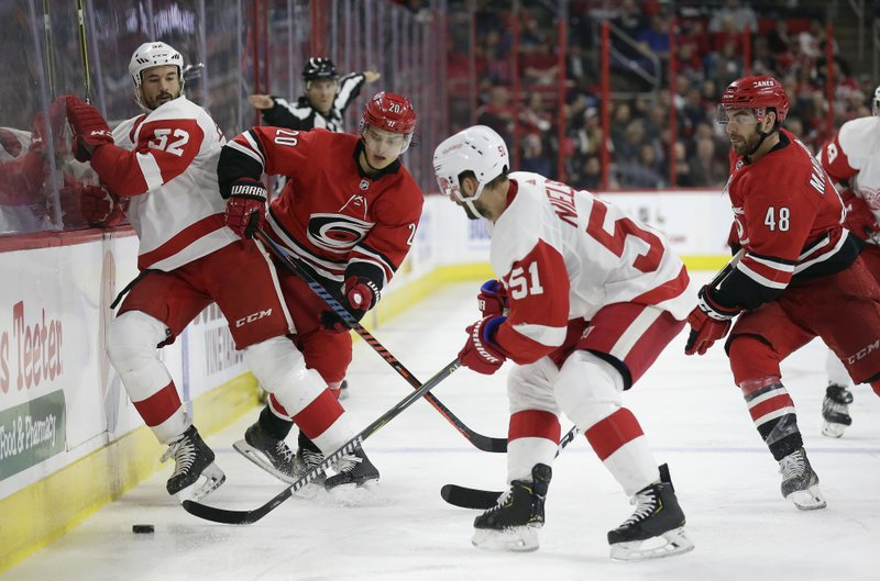Detroit Red Wings' Jonathan Ericsson (52), of Sweden, and Carolina Hurricanes' Sebastian Aho (20), of Finland, chase the puck with Red Wings' Frans Nielsen (51), of Denmark, and Hurricanes' Jordan Martinook (48) during the second period of an NHL hockey game in Raleigh, N. (AP Photo/Gerry Broome)