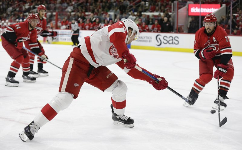 Detroit Red Wings' Christoffer Ehn, of Sweden, takes a shot on goal while Carolina Hurricanes' Justin Faulk (27) defends during the first period of an NHL hockey game in Raleigh, N. (AP Photo/Gerry Broome)