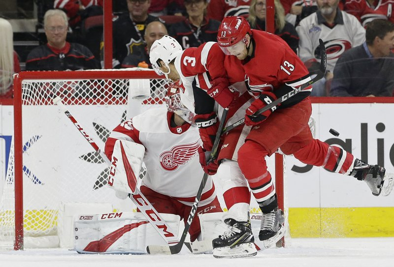 Detroit Red Wings' Nick Jensen (3) and goalie Jonathan Bernier defend the net in front of Carolina Hurricanes' Warren Foegele (13) during the first period of an NHL hockey game in Raleigh, N. (AP Photo/Gerry Broome)