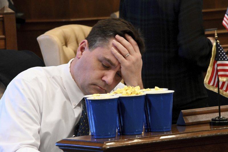 Sen Pat Colbeck, R-Canton is stocked-up with popcorn, but holds his head in his hands, facing a long night as the Michigan senate considers a flurry of bills on what should be the last day of the