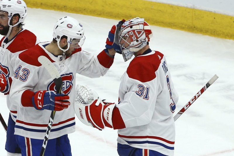 Montreal Canadiens goaltender Carey Price (31) celebrates his win against the Arizona Coyotes with Canadiens center Michael Chaput (43) as time expires in the third period of an NHL hockey game Thursday, Dec. (AP Photo/Ross D. Franklin)